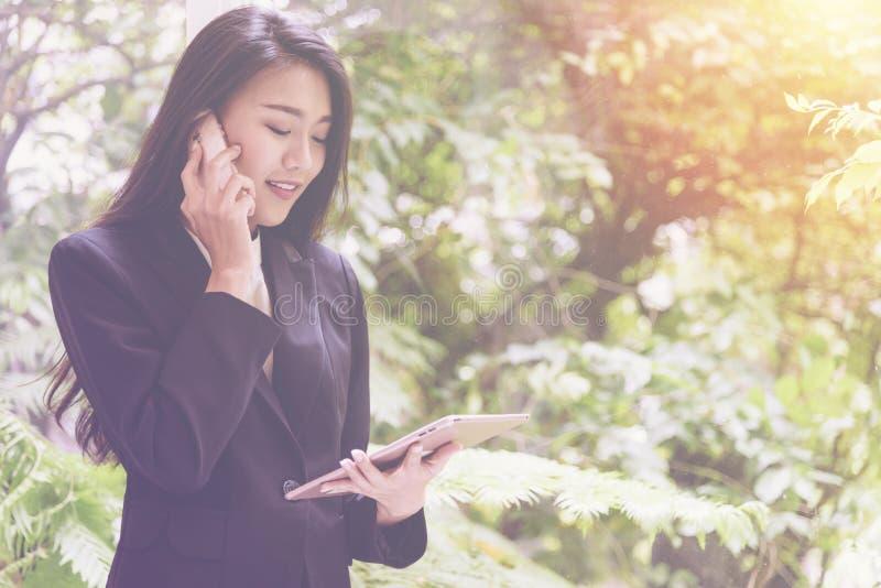 La mujer de negocios joven elegante que usa la tableta y hablando en el teléfono hace una pausa la ventana para se relaja, mirand fotografía de archivo libre de regalías