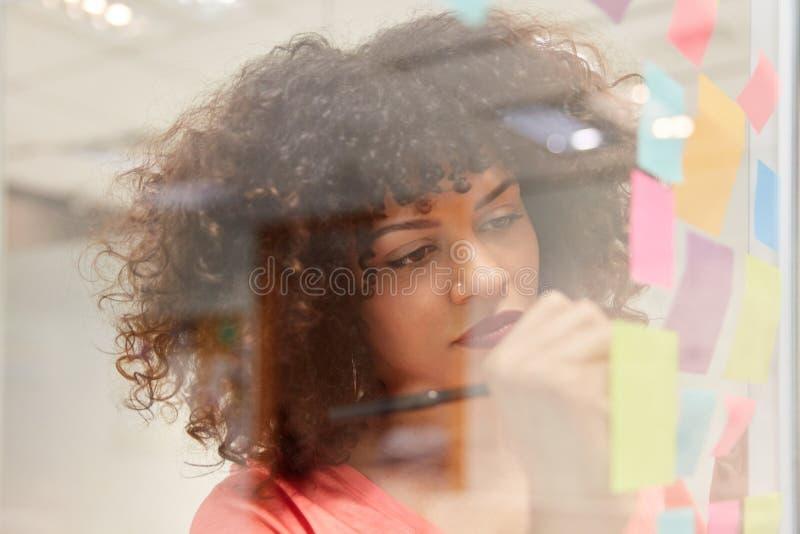 La mujer de negocios joven escribe ideas en notas pegajosas foto de archivo