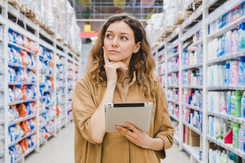 La mujer de negocios joven está pensando en compras con una tableta a disposición en un supermercado fotos de archivo libres de regalías