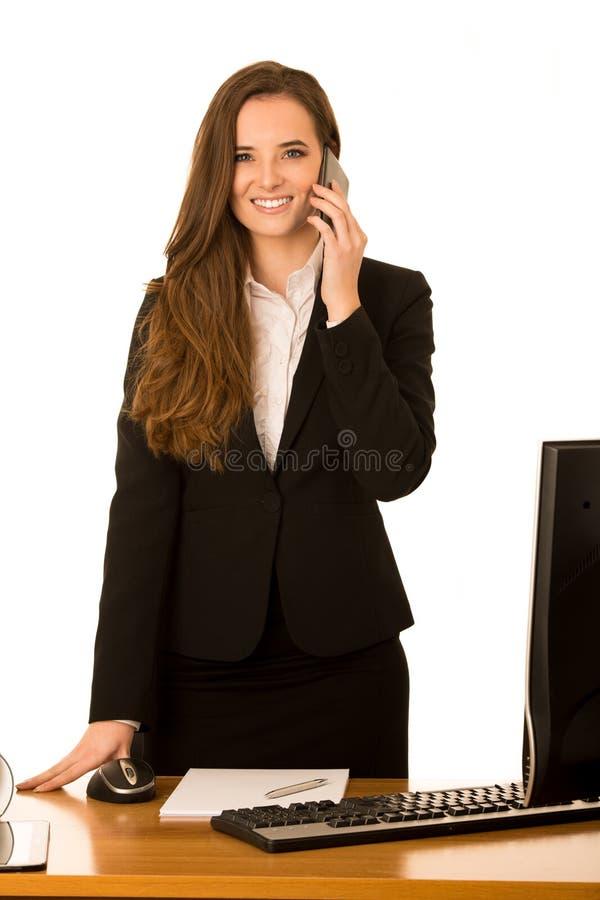 La mujer de negocios joven hermosa habla en el teléfono en su oficina fotografía de archivo libre de regalías
