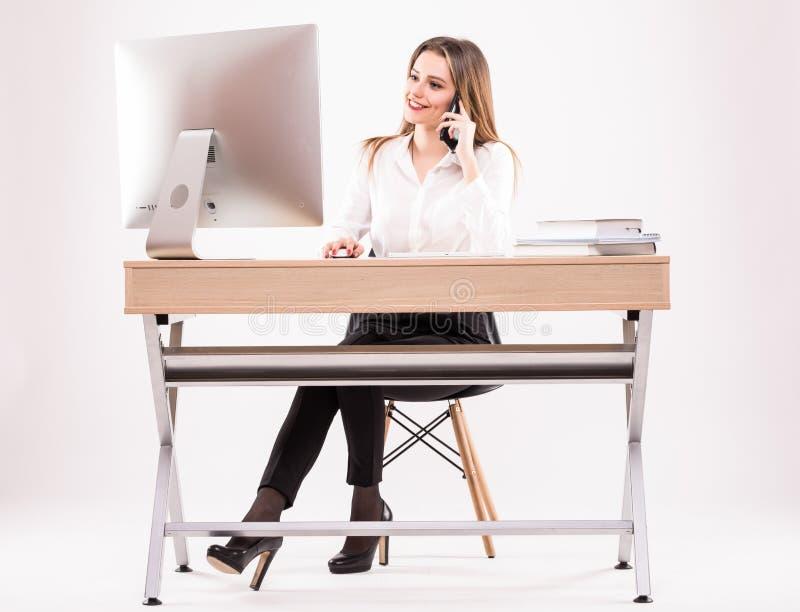 La mujer de negocios joven hermosa habla en el teléfono en su oficina aislada en el fondo blanco foto de archivo libre de regalías