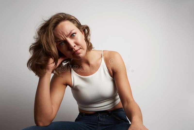 La mujer de negocios joven incurrió en una equivocación, foto del estudio en un fondo blanco foto de archivo