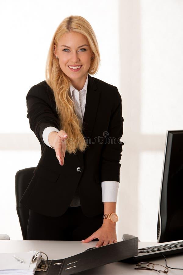 La mujer de negocios joven ofrece la mano al resolver la nueva persona o muestra imagen de archivo libre de regalías