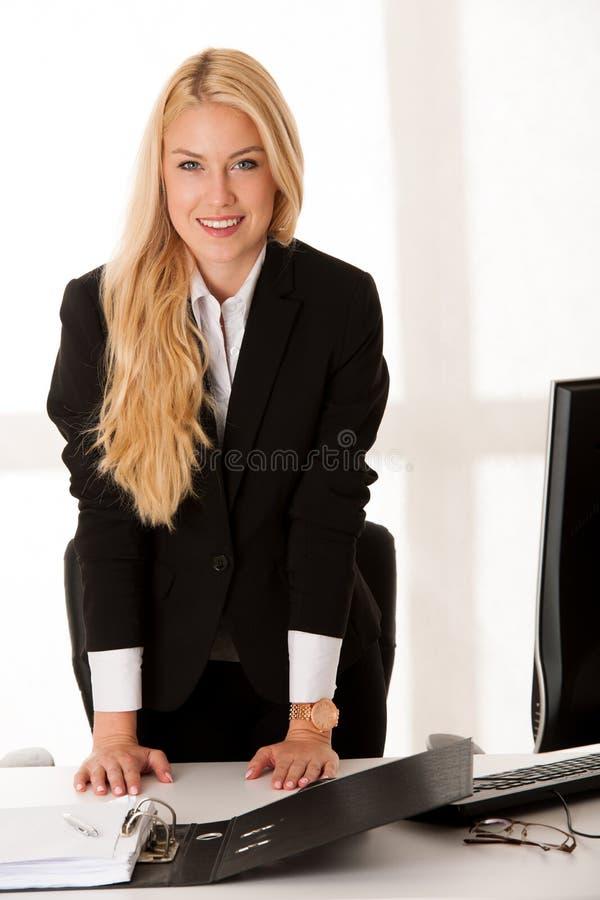 La mujer de negocios joven ofrece la mano al resolver la nueva persona o muestra imagenes de archivo