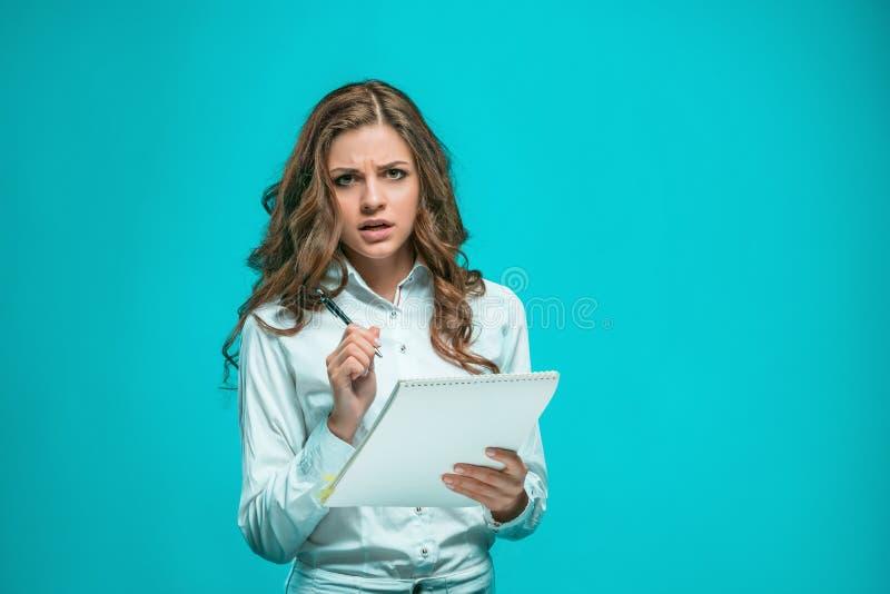 La mujer de negocios joven pensativa con la pluma y tableta para las notas sobre fondo azul imagen de archivo libre de regalías