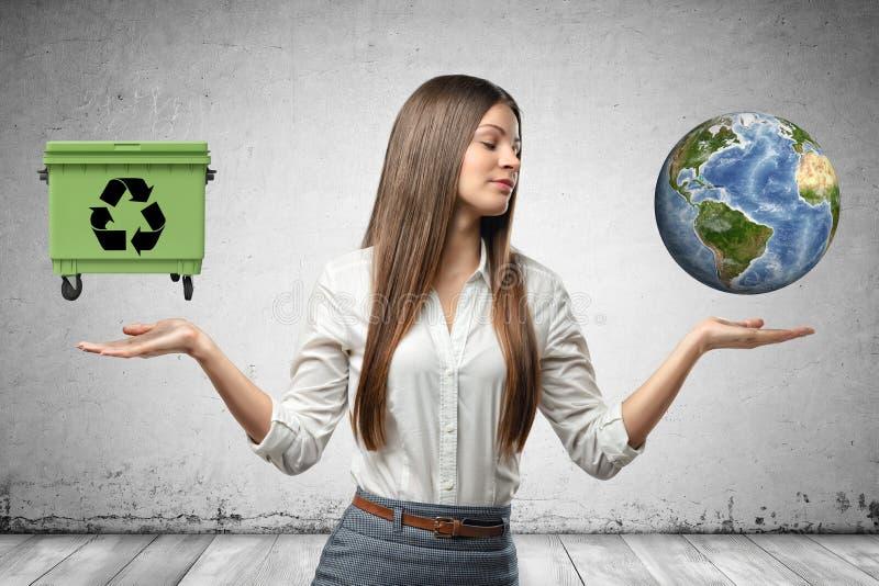 La mujer de negocios joven que sostiene el globo de la tierra y verde bote de basura en sus manos en fondo gris de la pared fotografía de archivo libre de regalías