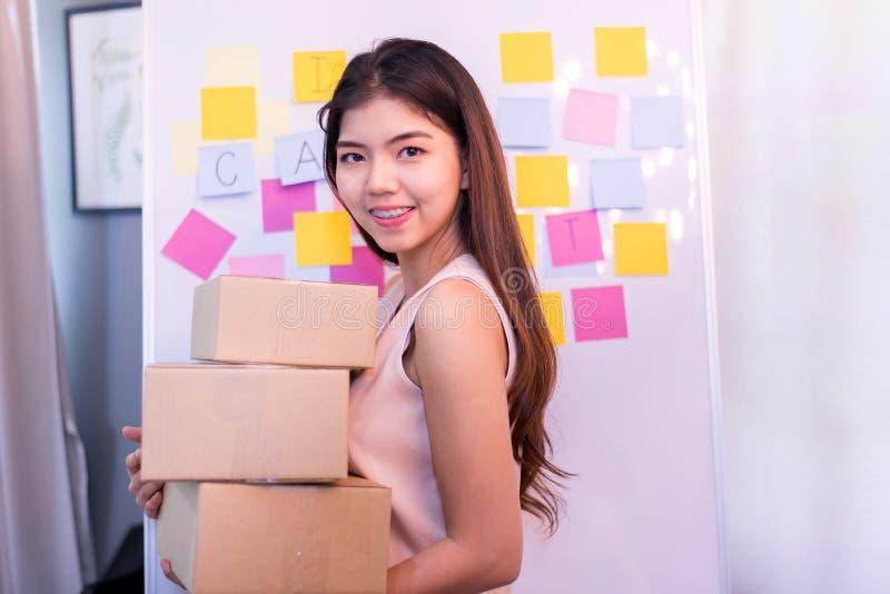 La mujer de negocios joven que sostiene un paquete para preparar la entrega, comienza al pequeño empresario foto de archivo