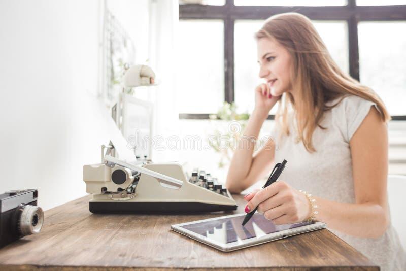 La mujer de negocios joven que trabaja en casa y dibuja en la tableta Espacio de trabajo escandinavo creativo del estilo imágenes de archivo libres de regalías