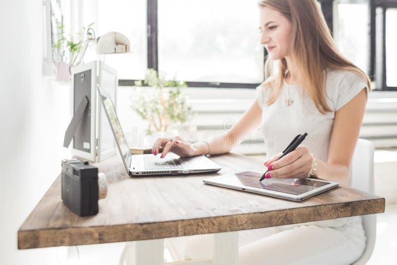 La mujer de negocios joven que trabaja en casa y dibuja en la tableta Espacio de trabajo escandinavo creativo del estilo imagen de archivo