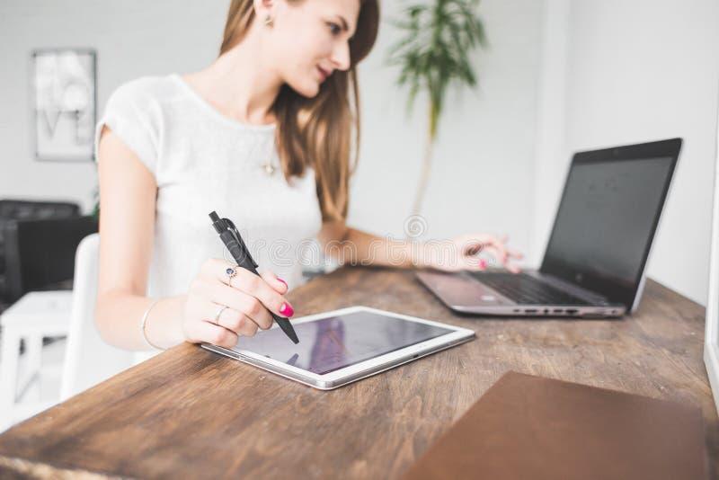 La mujer de negocios joven que trabaja en casa y dibuja en la tableta Espacio de trabajo escandinavo creativo del estilo imagen de archivo libre de regalías