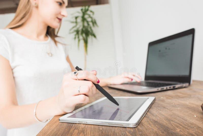 La mujer de negocios joven que trabaja en casa y dibuja en la tableta Espacio de trabajo escandinavo creativo del estilo fotografía de archivo libre de regalías