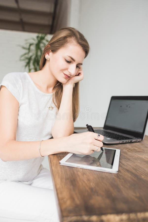 La mujer de negocios joven que trabaja en casa y dibuja en la tableta Espacio de trabajo escandinavo creativo del estilo fotografía de archivo
