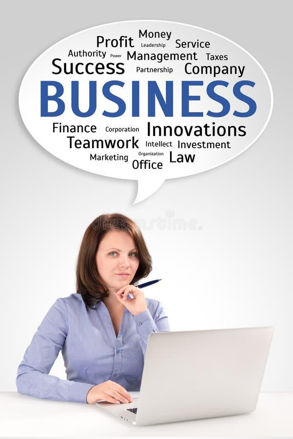 La mujer de negocios joven se está sentando delante de un ordenador portátil bajo speec foto de archivo