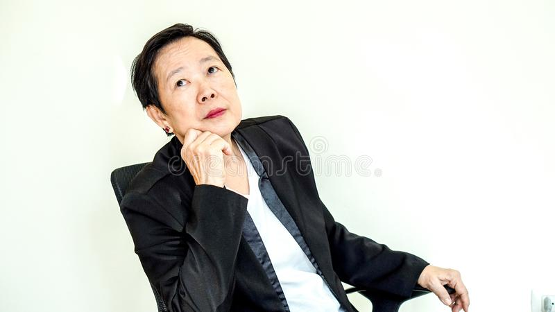 La mujer de negocios mayor asiática se sienta en silla que piensa en manageme foto de archivo libre de regalías
