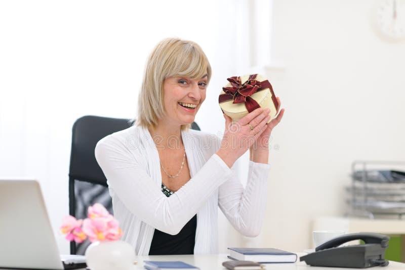 La mujer de negocios mayor feliz consiguió presente en la oficina foto de archivo libre de regalías