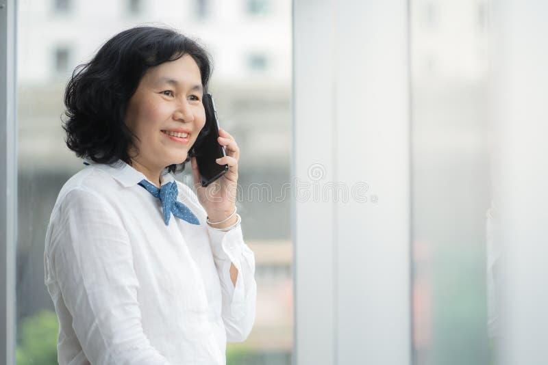 La mujer de negocios media asiática está llamando imagen de archivo libre de regalías