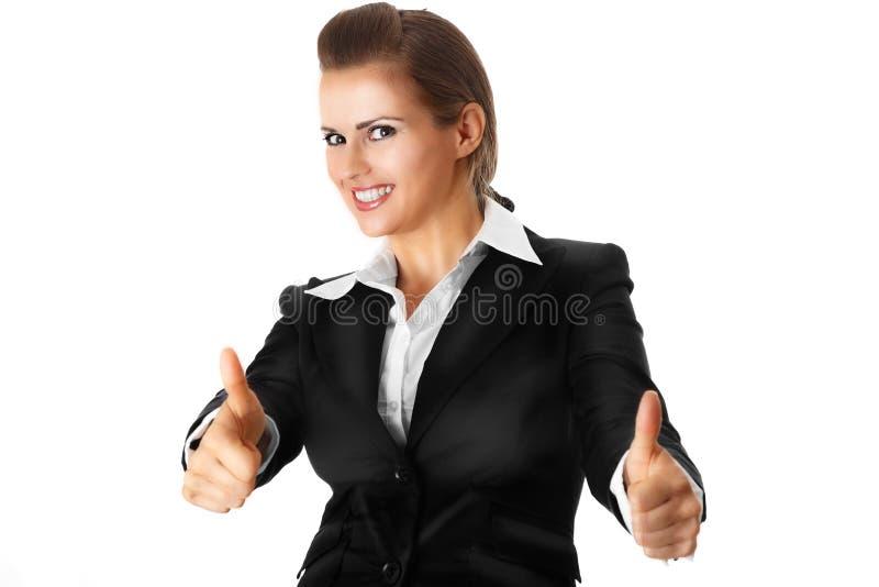 La mujer de negocios moderna sonriente que muestra los pulgares sube la GE imagenes de archivo