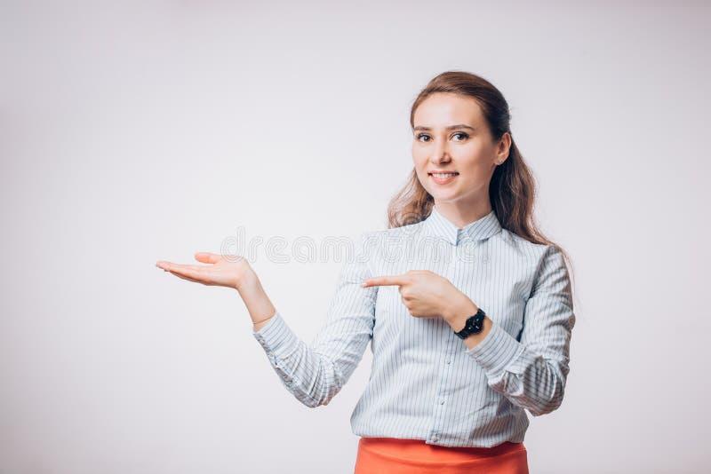 La mujer de negocios morena joven presenta el producto, muestra su mano al espacio vacío, fotos de archivo