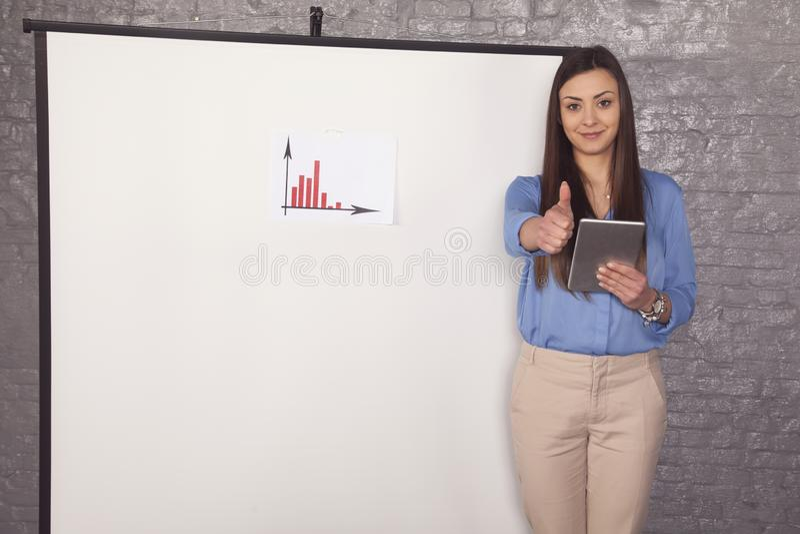 La mujer de negocios muestra los pulgares para arriba, carta del aumento imagen de archivo