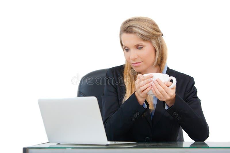 La mujer de negocios profesional joven mira el ordenador portátil y bebe el café imagen de archivo libre de regalías