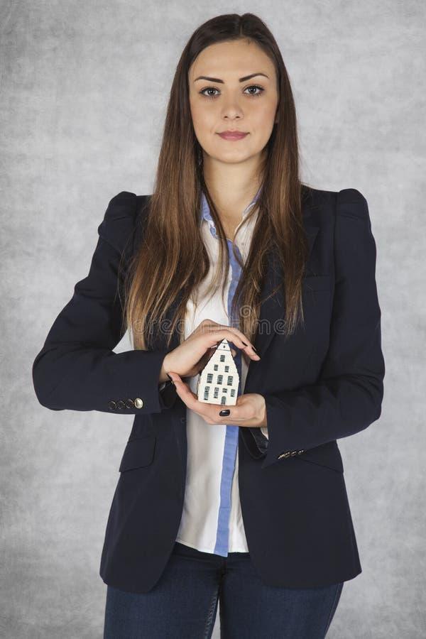 La mujer de negocios protege su propiedad, seguro foto de archivo