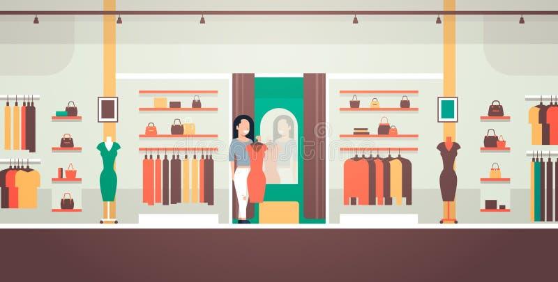 La mujer de negocios que intenta en la mujer elegante del nuevo vestido que mira la ropa femenina de la tienda de la moda del esp ilustración del vector