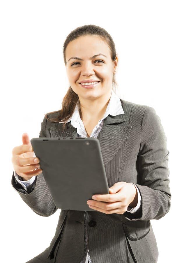 La mujer de negocios que mira la cámara con la tableta en manos hace tabletas la sonrisa imagen de archivo