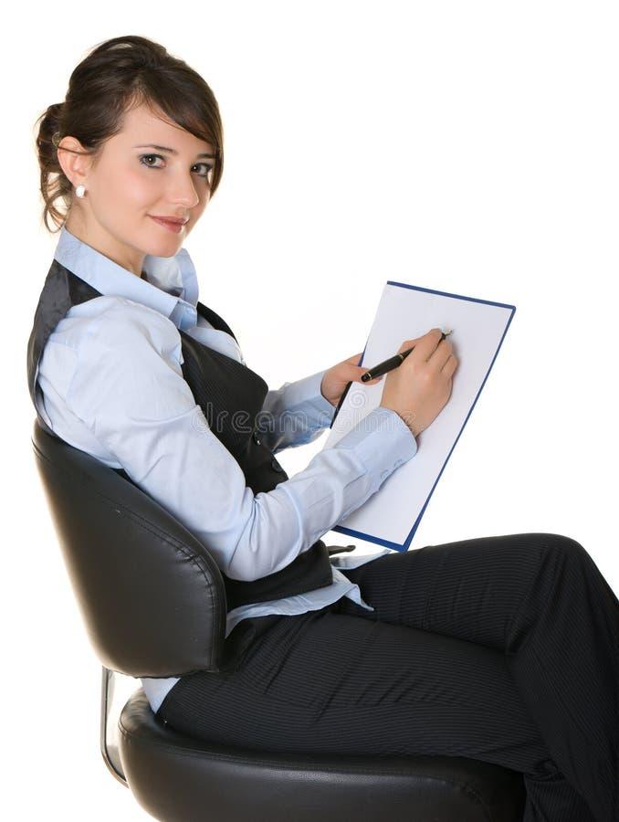 La mujer de negocios que se sienta en una silla y escribe foto de archivo