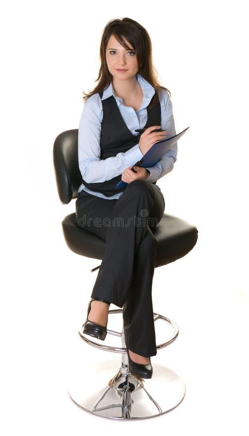 La mujer de negocios que se sienta en una silla y escribe imagen de archivo libre de regalías