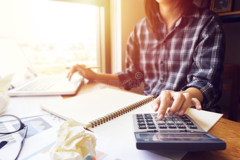 La mujer de negocios que usa la calculadora en la oficina para calcula la contabilidad foto de archivo