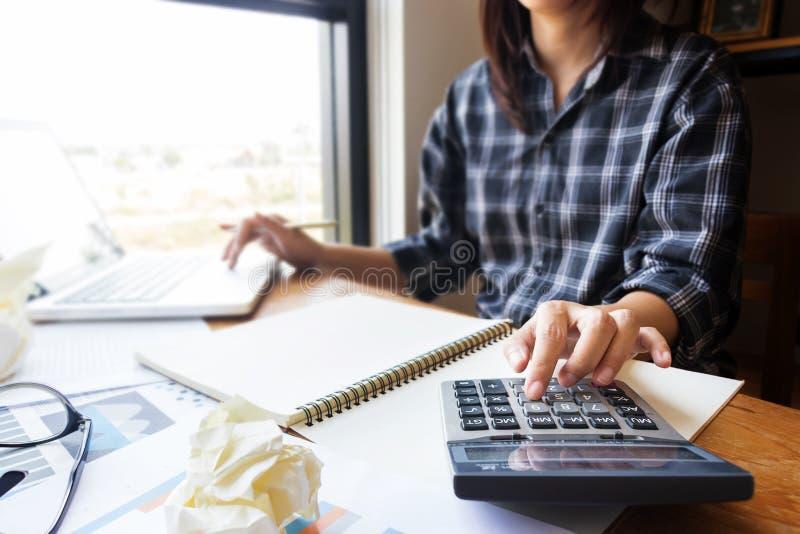 La mujer de negocios que usa la calculadora en la oficina para calcula la contabilidad y financiero como trabajo del contable foto de archivo