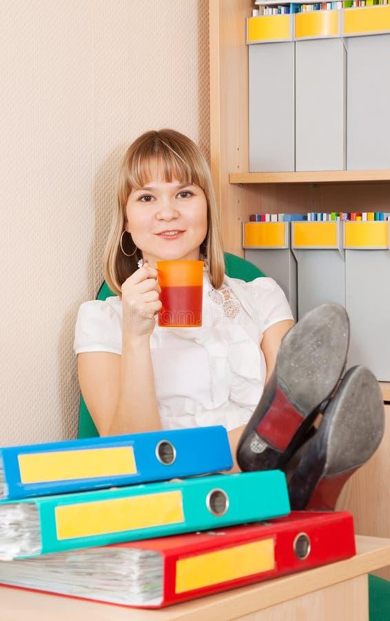 La mujer de negocios se está relajando en oficina foto de archivo libre de regalías
