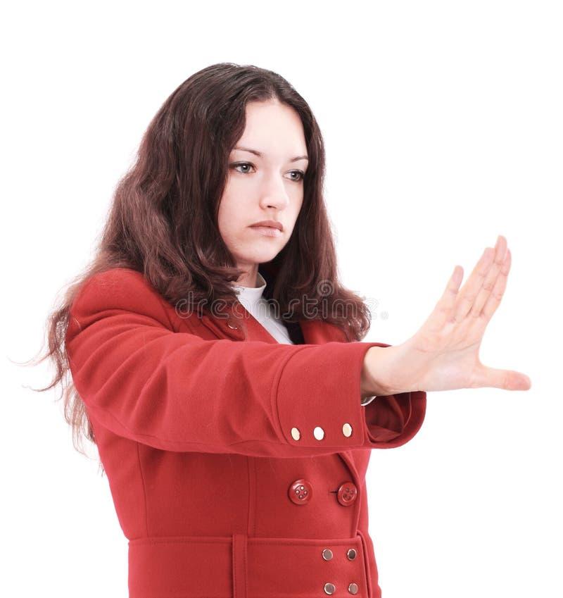 La mujer de negocios seria que hace la parada firma encima el blanco, foco a mano imágenes de archivo libres de regalías
