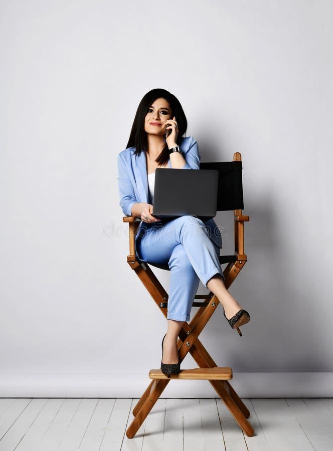 La mujer de negocios sonriente en el pantsuit oficial azul que se sienta con el ordenador portátil en la alta butaca tiene una ch fotos de archivo