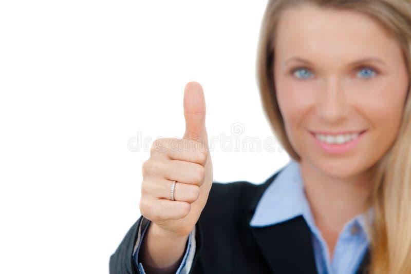 La mujer de negocios sonriente que muestra los pulgares sube la muestra fotografía de archivo