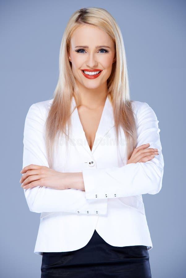Mujer de negocios sonriente que presenta con los brazos cruzados imagenes de archivo