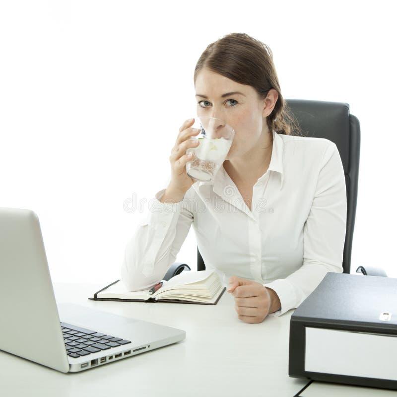 La mujer de negocios triguena joven es agua potable fotografía de archivo