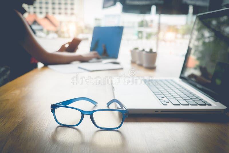 La mujer de negocios utiliza el ordenador portátil y el smartphone fotografía de archivo