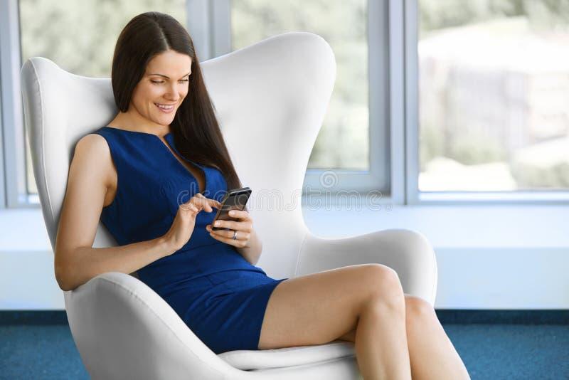La mujer de negocios utiliza el teléfono celular en la oficina Hombres de negocios fotos de archivo