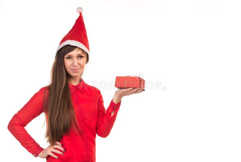 La mujer de pelo largo en casquillo rojo de la Navidad sostiene la caja de regalo roja imagen de archivo