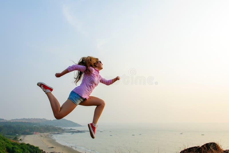 La mujer de pelo oscuro joven feliz hermosa salta alto y hace los movimientos dinámicos Muchacha deportiva en camisa, pantalones  imágenes de archivo libres de regalías