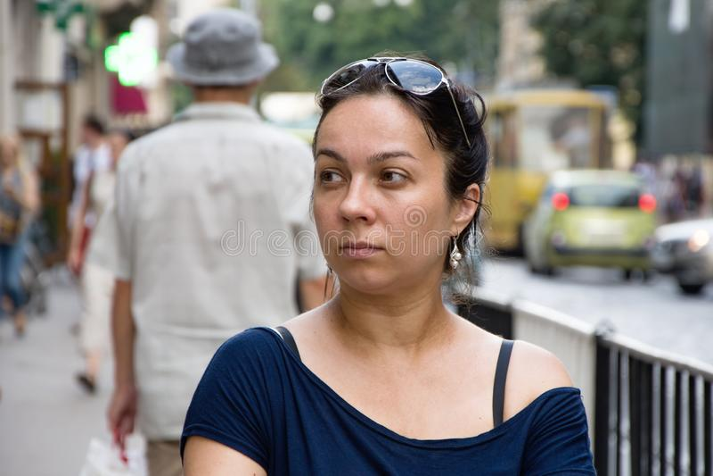La mujer de pelo oscuro sola mira cuidadosamente y sonríe adentro de la calle europea imagen de archivo libre de regalías