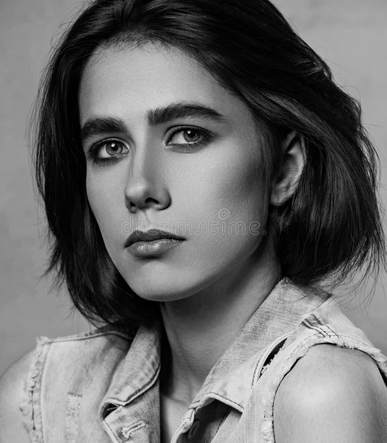 La mujer de pensamiento joven de la depresión triste que presenta en tejanos concede en fondo gris del estudio Retrato de la cara fotografía de archivo