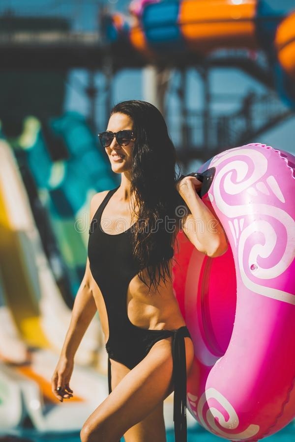 La mujer de risa con nadada suena cerca de piscina y de diapositivas fotos de archivo