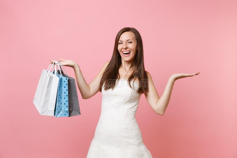 La mujer de risa de la novia en las manos blancas de la extensión del vestido que se casa sostiene bolsos coloreados multi de los imagen de archivo