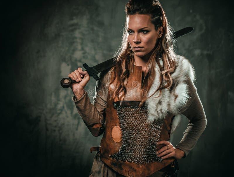 La mujer de Viking con el arma fría en un guerrero tradicional viste imágenes de archivo libres de regalías