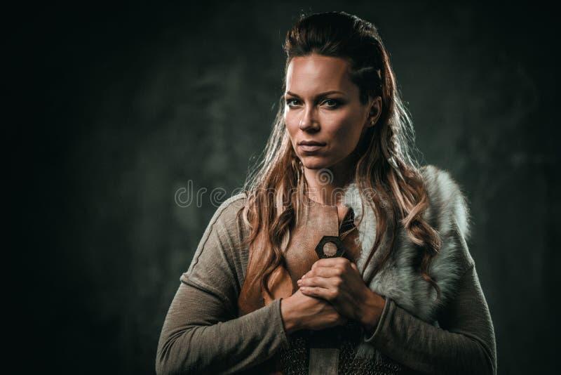 La mujer de Viking con el arma fría en un guerrero tradicional viste imagenes de archivo