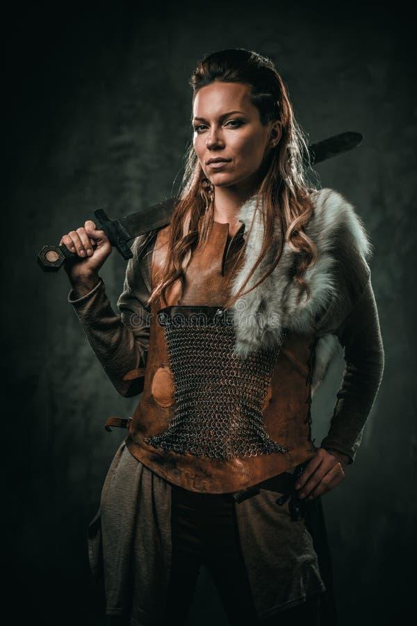 La mujer de Viking con el arma fría en un guerrero tradicional viste foto de archivo libre de regalías