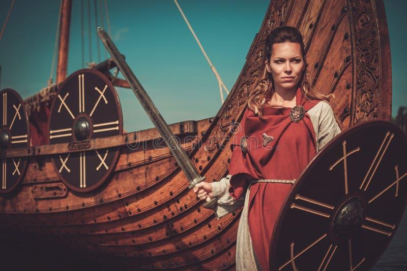 La mujer de Viking en ropa tradicional acerca a drakkar fotos de archivo