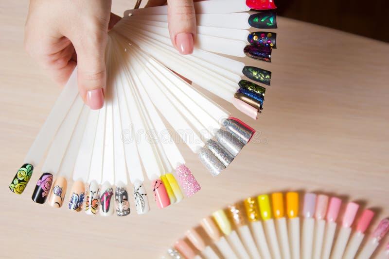 La mujer de la visión superior selecciona esmalte de uñas amarillo de la laca del color El técnico del clavo muestra la paleta de fotos de archivo
